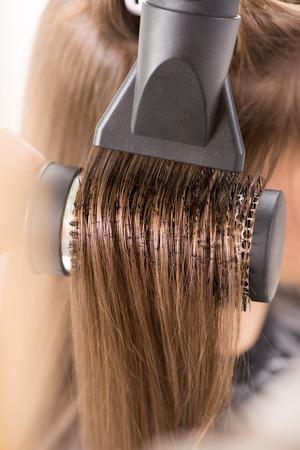 Sécher les cheveux longs bruns avec sèche-cheveux et une brosse ronde Banque d'images - 25727844