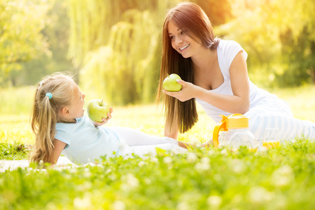 Beautiful Mother and daughter in the nature having little picnic  photo