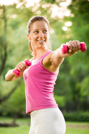 Beautiful young woman exercising with weights in the park  photo