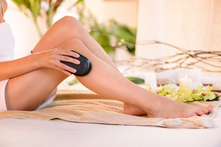 Young shapely woman sitting and massaging her legs with stone  photo