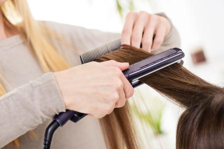 capelli castani: Parrucchiere raddrizzare lunghi capelli castani con ferri capelli