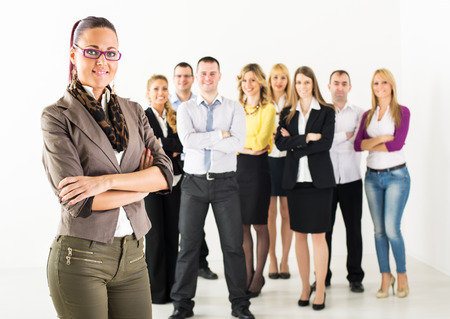 Smiling businesswoman standing in front of colleagues with crossed arm and looking at the camera  photo