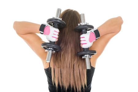 Sporty young woman doing exercise to strengthen her triceps with dumbbells. Stock Photo