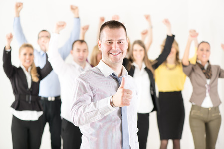 Successful businessman showing Thumbs Up standing in front of happy colleagues and looking at the camera. photo