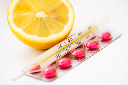 Medical thermometer, pills and lemon Stock Photo