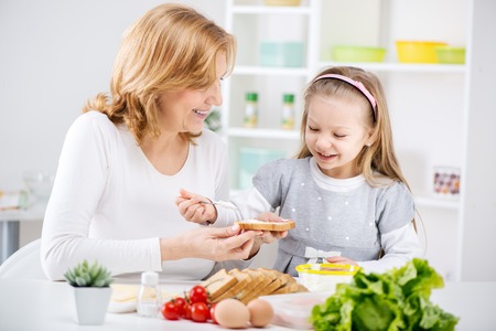 Beautiful happy grandmother and her cute granddaughter making Sandwich in the kitchen Stock Photo - 25856362