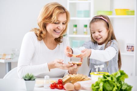 making a sandwich: Beautiful happy grandmother and her cute granddaughter making a Sandwich in the kitchen  Stock Photo