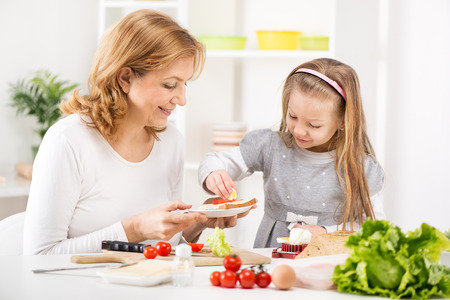 Cute little girl with Grandmother making a Sandwich in the kitchen  photo