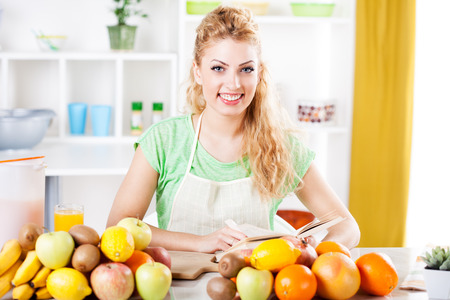 Beautiful young woman reading cookery book in a kitchen  Looking at camera  photo