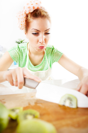 Beautiful young woman cutting kiwi in a kitchen   photo