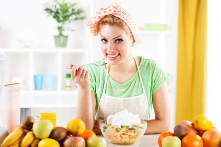 Beautiful young woman eat fruit salad with whipped cream in the kitchen  Looking at camera  photo