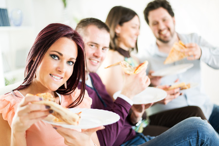 Group of happy friends sitting and eating pizza at Home Interior  photo