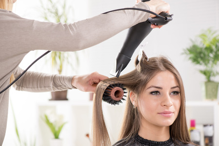 Hairdresser drying long brown hair with hair dryer and round brush