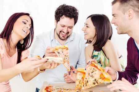 Group of happy friends sitting and eating pizza at Home Interior