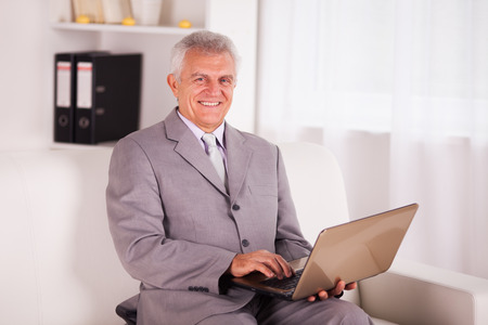 Happy Senior businessman working at home on laptop  photo