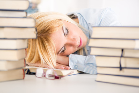 home schooling: Tired student fell a sleep between many books, while learning  Stock Photo