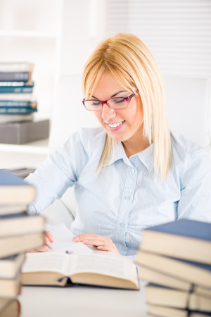 home schooling: Beautiful Student girl with glasses sitting with many books and marking text what need to learn