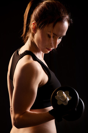 only the biceps: Beautiful woman with dumbbells standing on black and doing bicep exercises