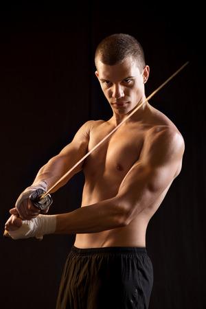 Young Man Holding Samurai Sword on Black  photo