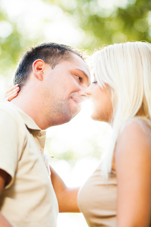 embraced: Beautiful embraced romantic couple in the park kissing each other in the front of sunlight  Stock Photo