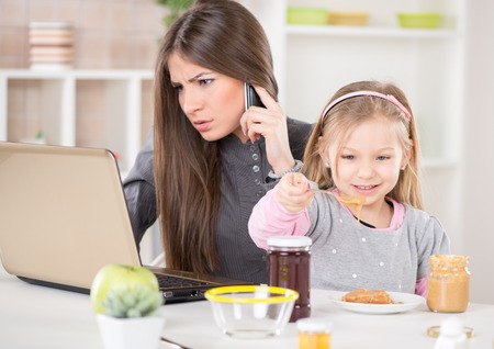 Overworked Business Woman and her little daughter in the morning  Mother read mail and make phone calls before going to work  Daughter smearing peanut butter on bread