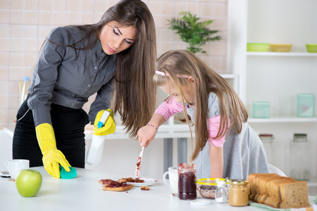 Angry Overworked businesswoman cleaning table in the morning and late for work, because her Daughter making mess with jam  photo
