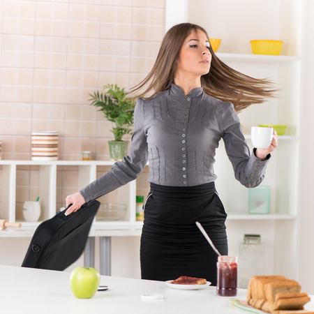 Businesswoman in the kitchen getting ready for work She is rushing for work Holding a bag with laptop in one hand and coffee in other Stock fotó