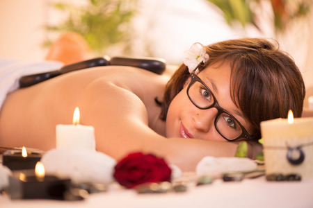 Young beautiful woman with glasses relaxing and enjoying at the spa center  photo