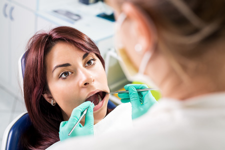 Dentist checking dental hygiene on patient in the office  photo