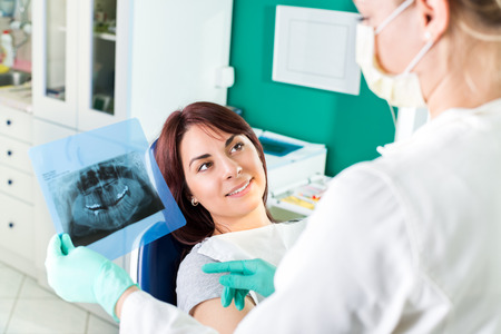Young female dentist showing to the patient X-ray picture in she s office  photo