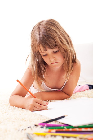 Cute little girl drawing with color crayons on the floor  photo