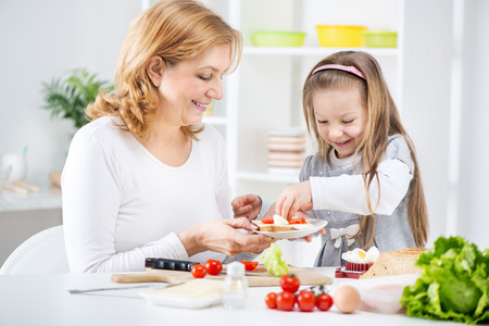 Beautiful happy grandmother and her cute granddaughter making Sandwich in the kitchen  photo