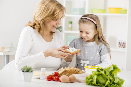 making a sandwich: Cute little girl with Grandmother making a Sandwich in the kitchen
