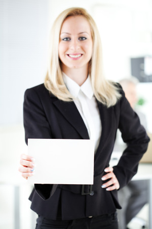 Beautiful young businesswoman holding Blank business card in the office. Looking at camera. Selective Focus. Focus on paper. photo