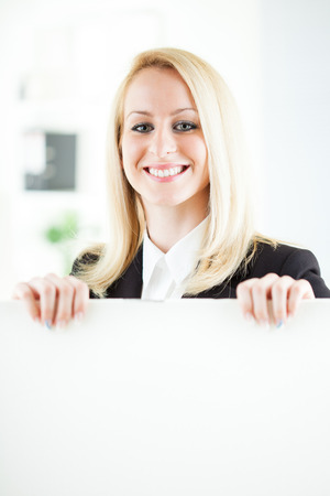 Beautiful young businesswoman holding Blank business board in the office. Looking at camera. Selective Focus. photo