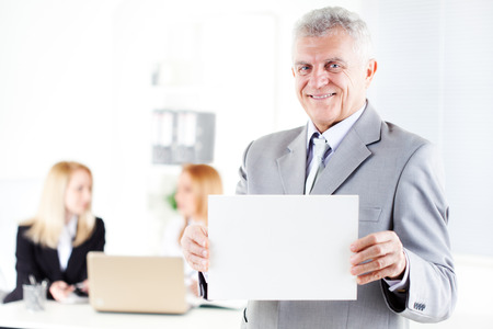 Happy senior businessman holding Blank business card in the office. Looking at camera. Selective Focus. photo