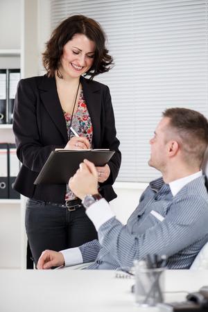 dictating: La gente de negocios feliz trabajando juntos en la oficina. Manager con su secretaria. �l est� dictando algo a ella. Foto de archivo