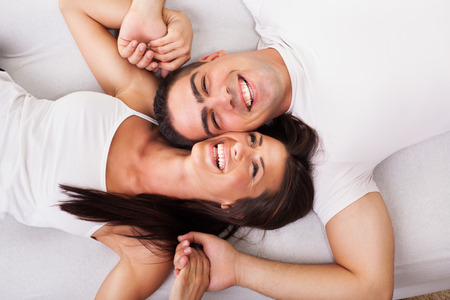 dating and romance: Romantic young couple Lying Down in bed. View from above.