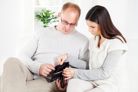 empty wallet: Young couple sitting worried in living room with Empty wallet.  Stock Photo