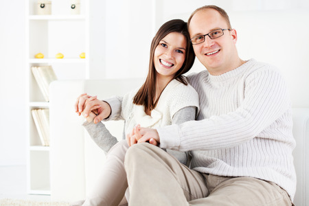 Happy beautiful Young couple is holding hands in home interior. Looking at camera. photo