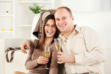 Happy Young couple sitting embraced at home, smiling and drinking  champagne. photo