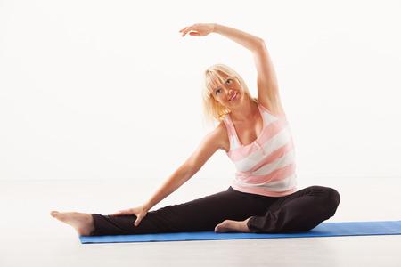 Beautiful mature woman doing Yoga Revolved Head to Knee Pose. Stock fotó