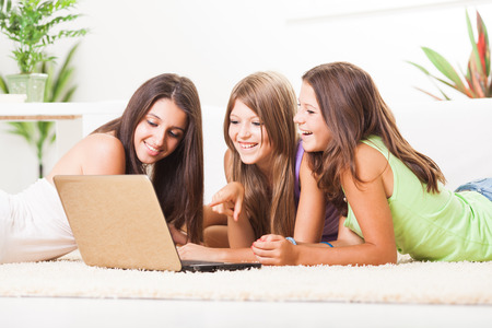 girl lying down: Beautiful teenage girls lying on the carpet with laptop and surfing in the internet