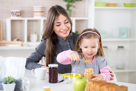 Cute little girl sitting in the mother lap and smearing peanut butter on bread  Banque d'images