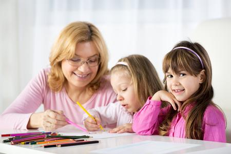 cute little girls: Dos ni�as lindas de dibujo con l�pices de colores en casa con la abuela.
