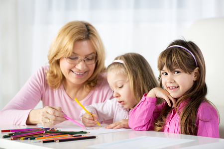 Two cute little girls drawing with colored pencils at home with Grandmother. photo