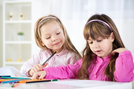 cute little girls: Dos ni�as lindas de dibujo con l�pices de colores en casa.