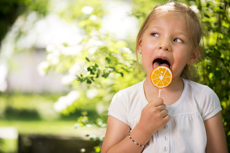Portrait of Cute Little Girl Standing in the Park and holding in hand orange Lollipop. photo