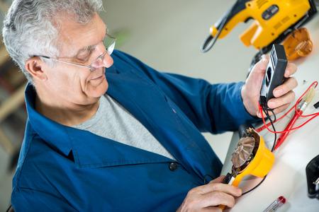 Senior adult Electrician using Digital Voltmeter for Testing Voltage on old hair dryer. photo