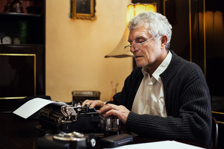 writing on glass: Retro Senior man writer with glasses writing on Obsolete Typewriter. Stock Photo